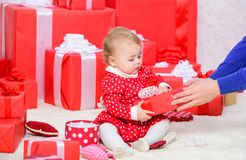 Baby first christmas once in lifetime event. Little baby play near pile of wrapped red gift boxes. Gifts for child first. Christmas. My first christmas. Sharing stock photos