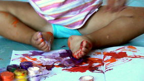 Baby first draws colored oil paints on a paper and overturns them stock footage