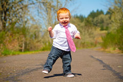 Baby First Steps. A one year old boy taking some of his first steps outdoors on a path with selective focus while wearing a nice shirt and a necktie Stock Photos