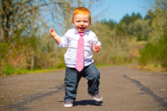 Baby First Steps. A one year old boy taking some of his first steps outdoors on a path with selective focus while wearing a nice shirt and a necktie Stock Photo
