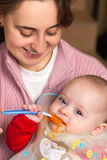 Baby first time eating alone. Adorable baby boy first time eating alone Stock Photography