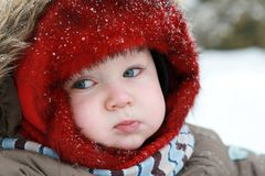 Baby first winter. A little baby boy in the snow on a cold winter day. First winter for baby Royalty Free Stock Images