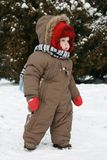Baby first winter. A little baby boy in the snow on a cold winter day. First winter for baby Royalty Free Stock Photo