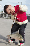 Baby fishing. Cute baby playing with a fish Royalty Free Stock Image