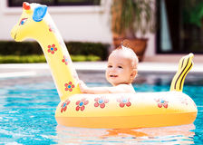 Baby with a float. Cute one year old baby swimming with a float in the swimming pool Stock Photography