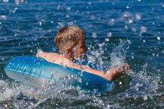 The boy floats in a rubber ring in the sea. Baby floats in terms of rescue at sea stock photo