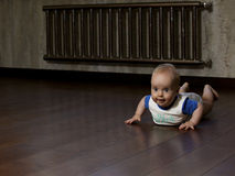Baby on the floor. Little smiling baby with grey eyes on the wooden floor at apartment room. Baby lying on the abdomen Royalty Free Stock Photo