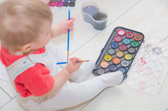 The baby on the floor playing with his paints. royalty free stock images