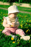 Baby with a flower on a grass. Little seriously child is sitting on the green grass with yellow flower in hands royalty free stock photo