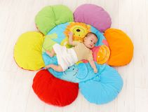 Baby on flower playmat. Baby lying on flower shape playmat, high angle royalty free stock photography