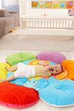 Baby on flowery playmat. Content baby lying on flowery playmat, with hands in mouth royalty free stock photography