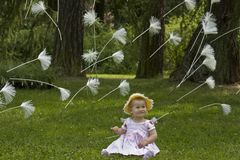 Baby with flying dandelion seeds Royalty Free Stock Photos