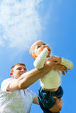 Baby flying on father's hands. Baby boy flying on his father's hands Stock Image