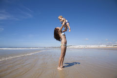 Baby flying in woman arms next to Conil Stock Image
