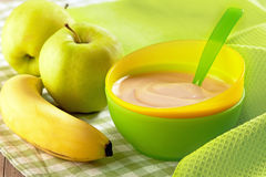 Baby food. Apple and banana puree in plastic bowl Stock Images