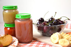 Baby food, baby fruit mashed in a glass jar, sliced carrot slices, apple, banana, cherry Stock Photo