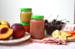 Baby food, baby fruit mashed in a glass jar, sliced carrot slices, peach, banana, cherry Stock Images