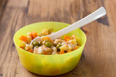 Baby food in bowl with spoon on brown background Royalty Free Stock Image
