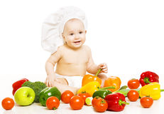 Baby food. Child in cook hat sitting inside vegetable over white royalty free stock image