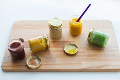 Vegetable or fruit puree or baby food in jars. Baby food, healthy eating and nutrition concept - vegetable or fruit puree or baby food in glass jars and feeding Stock Photos