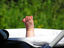 Baby foot. Sticking up from a carriage Stock Photo