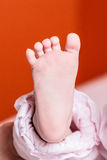 Baby Foot. One foot of a newborn baby in front of an orange background royalty free stock photography