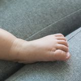 Baby foot on a gray sofa stock images