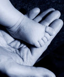 Baby foot on mans hand stock images