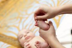 Baby foot massage Stock Photo