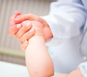 Baby foot massage Stock Photos