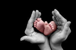 Baby foot in mother hands on black background.  Royalty Free Stock Photo