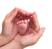Baby foot in mother hands on white background.  Royalty Free Stock Photography