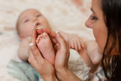 Baby foot in mother's hands Stock Photo