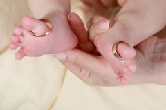 Baby foot in mother`s hands with care with rings on toes royalty free stock images