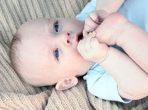 Baby with Foot in Mouth. Cute baby boy tastes his toes while lying on blanket Royalty Free Stock Images