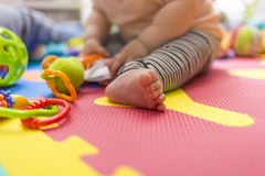 Baby foot playing on a colorful toy game ground Stock Photo