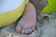 Baby foot playing in the sand. On a beach Stock Photo