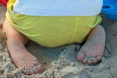 Baby foot playing in the sand. On a beach Royalty Free Stock Photography
