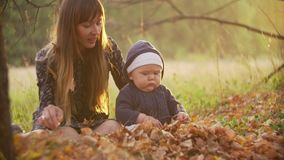 Baby in the forest. Autumn leaves. The kid with mother play in the wood. Mother with the child sit on yellow autumn stock footage