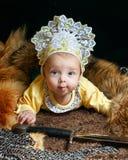 Baby, fox pelt and sword Royalty Free Stock Photo