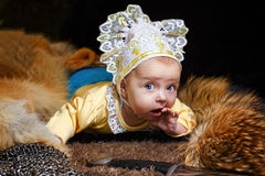 Baby, fox pelt and sword. Blue-eyed baby lying on fur litter near the hauberk and sword, fox pelt in the background Royalty Free Stock Photography