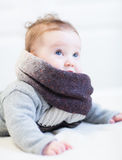 Baby in a frey knitted sweater and big brown scarf Royalty Free Stock Images