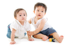 Baby friendships. Two lovely asian babies sitting on the floor stock photography
