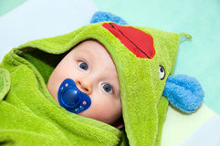 Baby in frog towel. With pacifier. Baby is looking straight into camera stock photography
