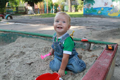 Baby fun playing with sand. Bright positive emotions. The little boy of the European (Slavic) appearance playing in the sandbox. The boy is 1,4 years Royalty Free Stock Photos