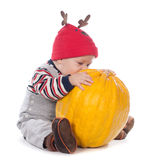 Baby in funny deer hat with orange pumpkin Royalty Free Stock Images