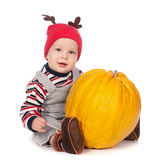 Baby in funny deer hat with orange pumpkin Royalty Free Stock Image