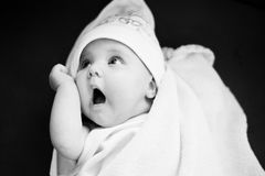 Baby with a funny face in a towel. Looking suprissed, black and white Stock Photo