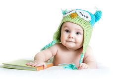 Baby in funny knitted hat owl with book Stock Images