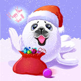 Baby fur seal in the cap Santa Claus and a bag with gifts Happy Stock Photo